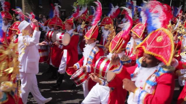 vídeos de stock e filmes b-roll de ws costumed marching band in notting hill carnival / london, united kingdom - cultura sul americana