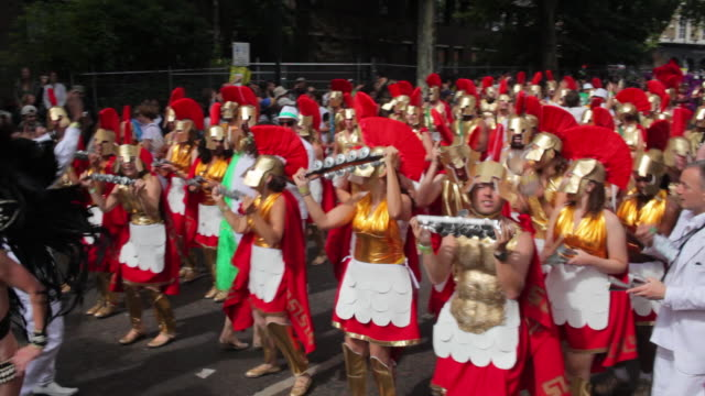 ws pan costumed marching band in notting hill carnival / london, united kingdom - notting hill videos stock videos & royalty-free footage