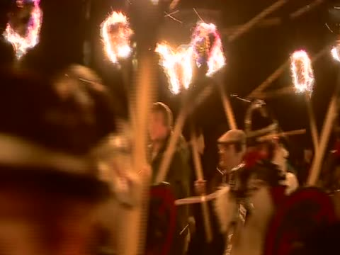costumed men carrying flaming torches parade in the streets of lerwick for the annual up helly aa festival - 社会史点の映像素材/bロール