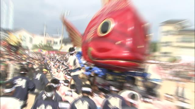costumed participants make a karatsukunchi hikiyama red sea bream float bob up and down at a parade. - フロート車点の映像素材/bロール