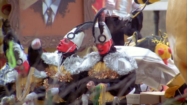 costumed participants ride a large skeleton float during the 1989 mardi gras parade in new orleans - festwagen stock-videos und b-roll-filmmaterial