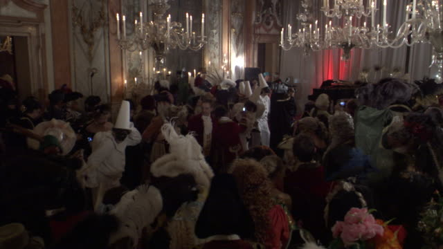 costumed party-goers gather in a ballroom. - ballroom stock videos & royalty-free footage