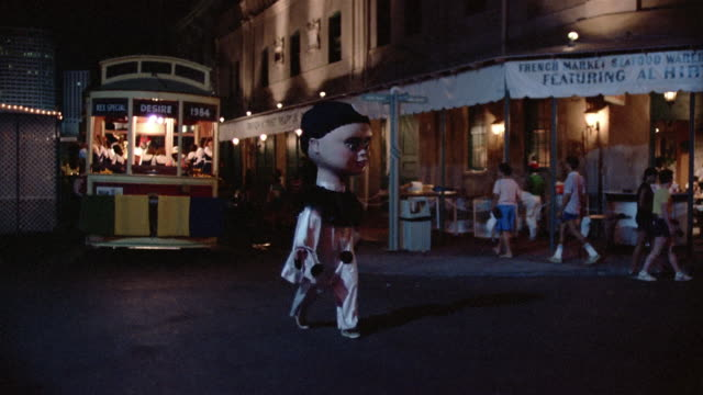 1984 ws costumed people marching in parade in front of streetcar named desire during annual mardi gras parade in the french quarter / new orleans, louisiana, usa - festwagen stock-videos und b-roll-filmmaterial