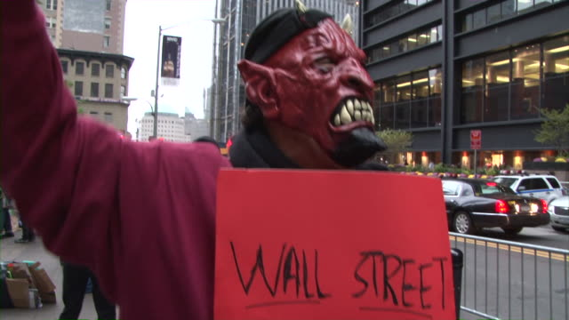 costumed protester holding up sign in zuccotti park during occupy wall street movement audio / new york city, new york, united states - occupy protests stock videos & royalty-free footage