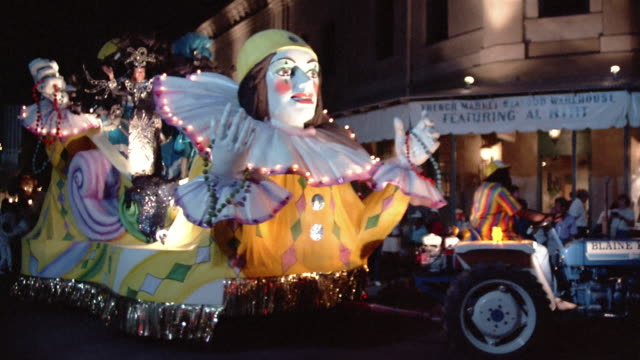 1984 la ws costumed woman dressed as queen riding on parade float and waving to spectators during annual mardi gras parade in the french quarter / new orleans, louisiana, usa - festwagen stock-videos und b-roll-filmmaterial
