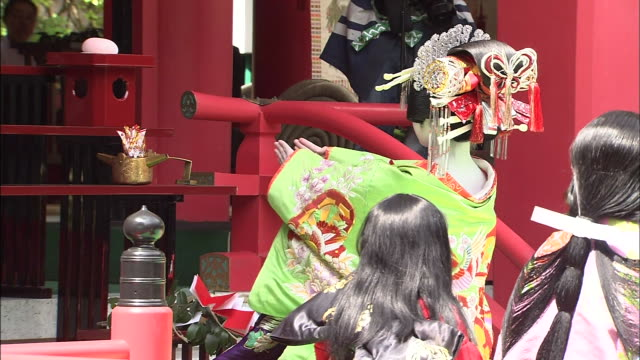 A costumed woman waves her arms and bows before a shrine.