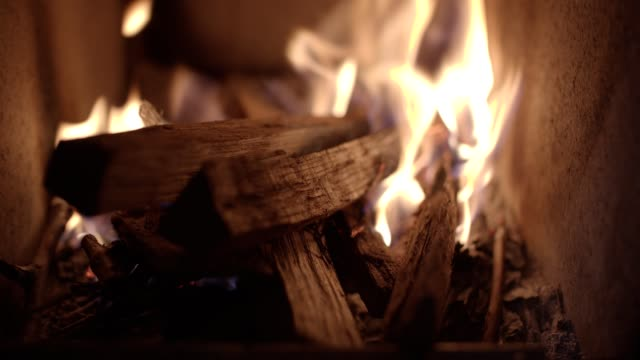 pov. cosy home relaxation in front of the fireplace. celebration time. fireplace with burning woods close-up. - cosy stock videos & royalty-free footage