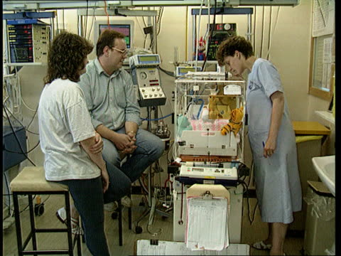 cot deaths science baby in incubator in special care unit with nurse and parents around readings on monitors mother reaching into incubator and... - kommode stock-videos und b-roll-filmmaterial