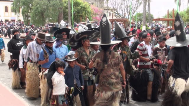 Cotacachi dancers pass by the village's main street, dancing and wearing big hats and fur pants.