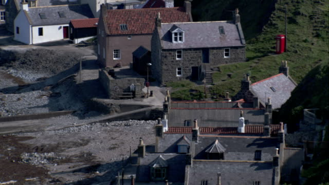 cottages line a narrow piece of land between the coastline and a hillside in crovie, scotland. available in hd. - クロヴィー点の映像素材/bロール
