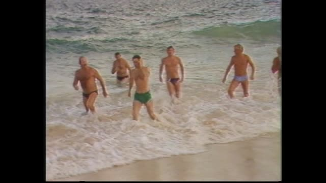 stockvideo's en b-roll-footage met prince charles in board shorts and bare chested walks towards beach / charles catches wave body surfing / press charles in water – see bald spot in... - 1983