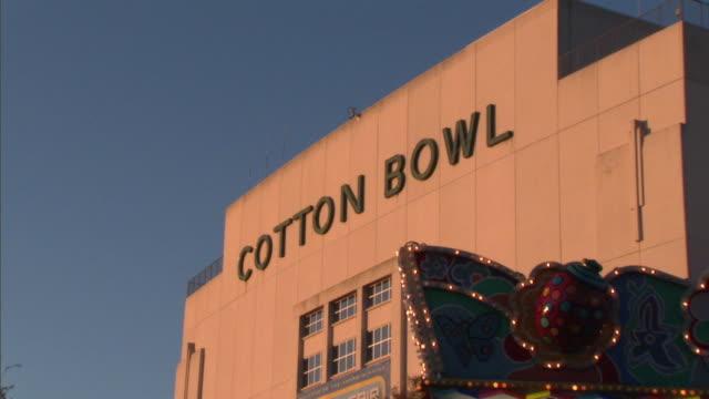 CU ZO MS Cotton Bowl building and illuminated kiosk in amusement park, Dallas, Texas, USA