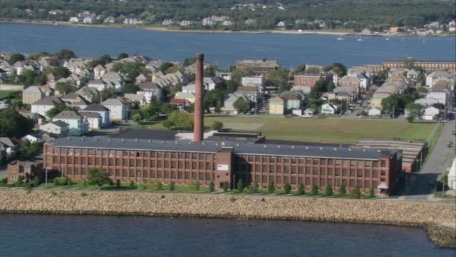 aerial cotton mill on the shoreline, town beyond / new bedford, massachusetts, united states - new bedford stock videos & royalty-free footage