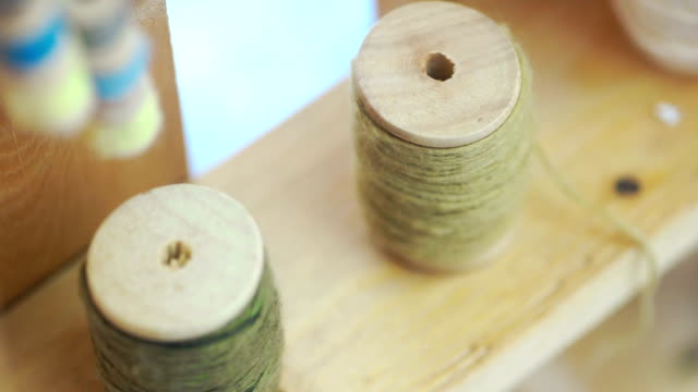 Cotton thread spool on a wooden background.