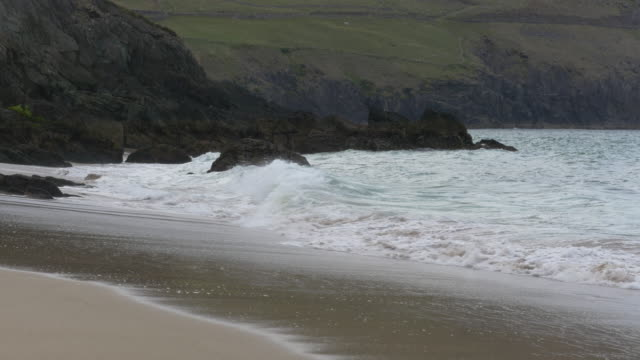 WS Coumeenole Beach and Atlantic Ocean, sandy beach, waves crashing on rocky Irish shoreline, Dingle Peninsula, Ireland