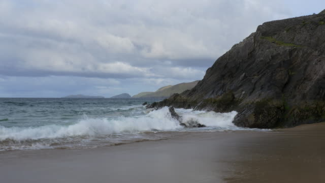 WS Coumeenole Beach and Atlantic Ocean, waves, rocky Irish shoreline and nice clouds, islands, Dingle Peninsula, Ireland