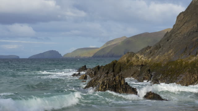 MS Coumeenole Beach and Atlantic Ocean, waves, rocky Irish shoreline and nice clouds, islands, Dingle Peninsula, Ireland