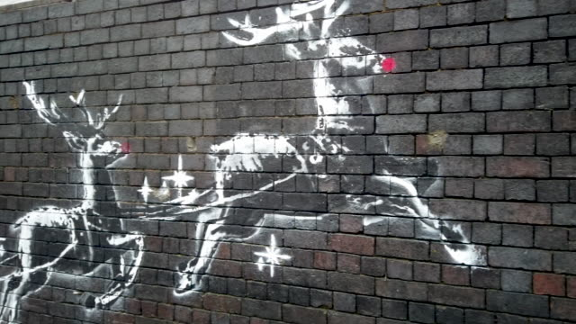 council worker stands guard as red noses have appeared on banksy's birmingham homeless reindeer mural , which has also been fenced off to protect the... - arts culture and entertainment stock videos & royalty-free footage