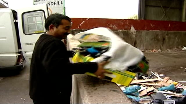 councils plan to link rubbish collection to council tax payments man along with box of rubbish at recycling centre and tips it into collection area... - kettenglied stock-videos und b-roll-filmmaterial