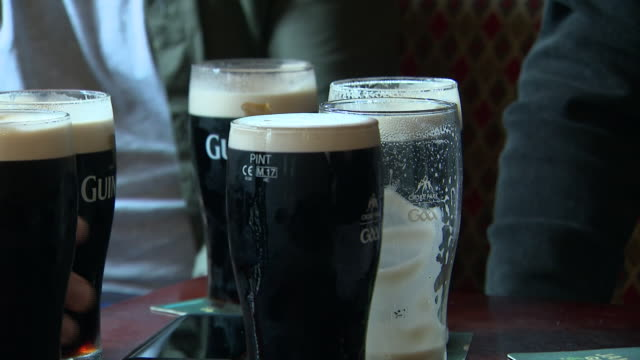 counrty enters phase 3 of a four-stage plan to lift covid-19 restrictions. shows: men drinking pints of guinness in a pub, people in a hair salon,... - dublin republic of ireland stock videos & royalty-free footage