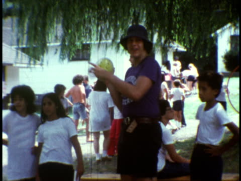 1973 MS Counselor playing football and hoop at Camp Sussex summer camp / Sussex, New Jersey