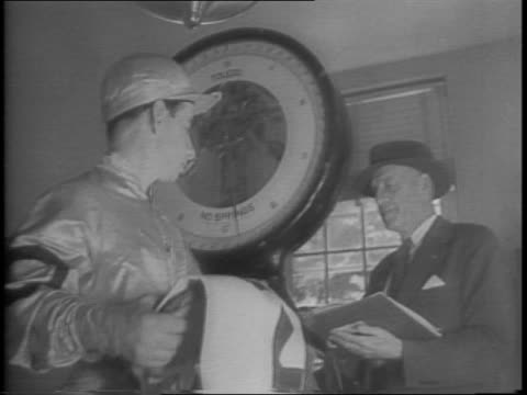 count fleet adds belmont to his clean sweep of 1943 biggest 3year old championships / jockey johnny longden getting dressed in silks for the race /... - 1943 stock videos and b-roll footage
