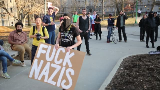 vídeos de stock, filmes e b-roll de a counter protester to a group of white nationalist protesters calling themselves traditional youth holds a sign reading fuck nazis members of the... - bloomington indiana
