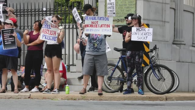 counter protesters ask drivers to 'honk if confederates suck,' as they protest against confederate heritage groups that rallied nearby the jefferson... - バージニア州 リッチモンド点の映像素材/bロール