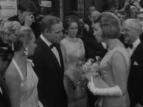 countess from hong kong' film premiere; england: london: carlton theatre: ext av neon lit board advertising film: tilt down to bv crowd and police... - sophia loren stock videos & royalty-free footage