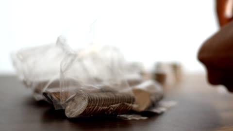 vídeos y material grabado en eventos de stock de contar monedas en una bolsa de plástico - bolsa de plástico