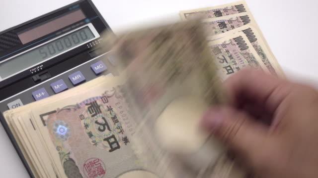 vídeos de stock, filmes e b-roll de contando ienes japoneses com calculadora - conta artigo de armarinho