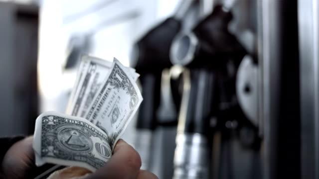 hd: conteggio del denaro per serbatoio del carburante - stazione di rifornimento video stock e b–roll