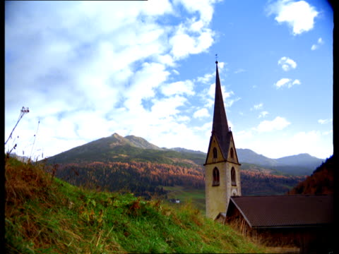 a country church steeple rises above mountains. - steeple stock videos & royalty-free footage