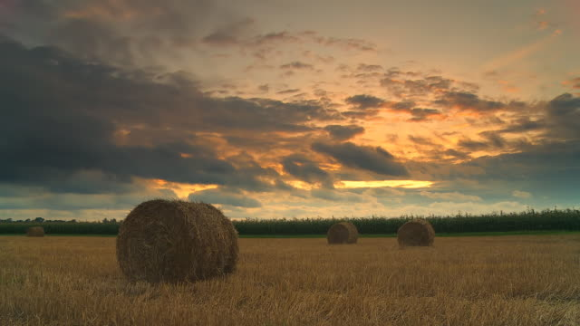 hd time lapse: country cloudscape at sunset - hay field stock videos & royalty-free footage