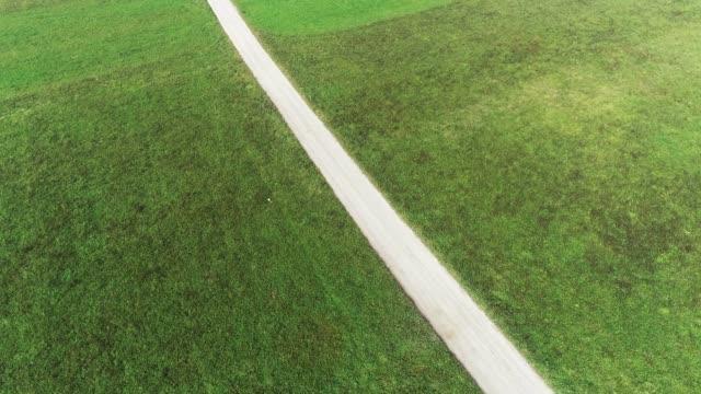 vidéos et rushes de country road divisant green meadow - image contrastée