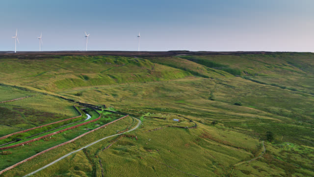 country road in pennines with wind turbines - drone shot - pennines stock videos and b-roll footage