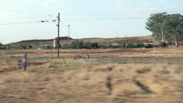 stockvideo's en b-roll-footage met a country road passes small villages and farmland in africa. - nederzettingen