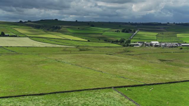 stockvideo's en b-roll-footage met land road passing farm in het peak district, engeland-drone shot - derbyshire
