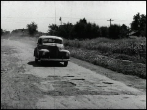vídeos de stock e filmes b-roll de country road with potholes; 1940 nash drives toward on road toward camera / looking through windshield at dirt road / weather eye heating control on... - para brisas