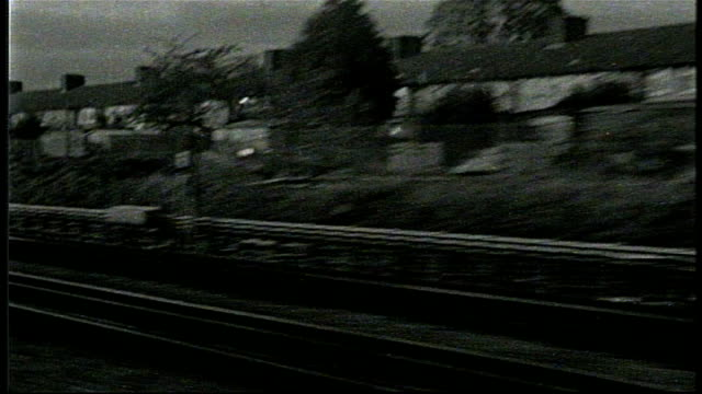 countryside as seen from moving train on bw super 8 film - zugperspektive stock-videos und b-roll-filmmaterial