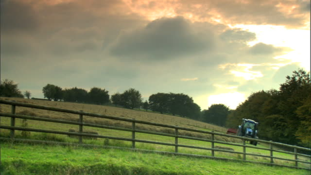 ws countryside farm land hill w/ wooden fence tractor pulling hay baler trees distant cloudy sky uk - hay baler stock videos & royalty-free footage