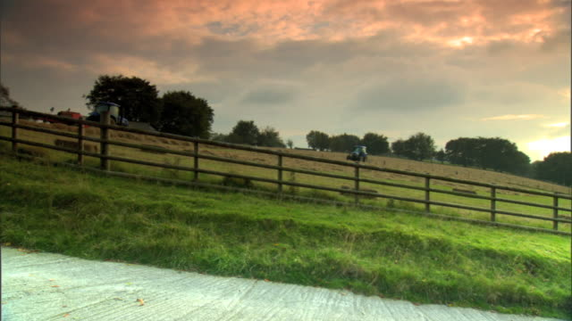 ws countryside farm land hill w/ wooden fence tractors on hill trees bg pink white cloudy sky uk - hay baler stock videos & royalty-free footage
