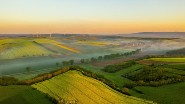 h/l landschaft bei morgennebel und windräder drehen sich in der ferne - motorisierte zeitrafferaufnahmen stock-videos und b-roll-filmmaterial