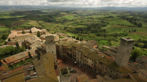 t/l ha ws countryside surrounding san gimignano with piazza della cisterna below / italy - town square stock videos & royalty-free footage