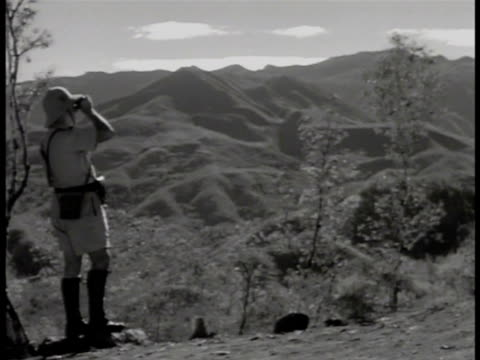 vidéos et rushes de countryside w/ buildings in distant hills, mountains bg. officer in summer uniform looking over mountain region w/ binoculars. free french soldiers... - dom tom