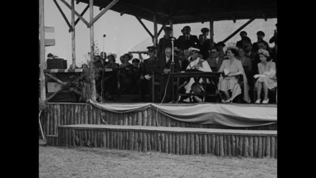 vídeos de stock e filmes b-roll de ws countryside with enormous crowd / king george vi and queen elizabeth the queen mother stand in open car as it passes through crowd in field queen... - dança da guerra
