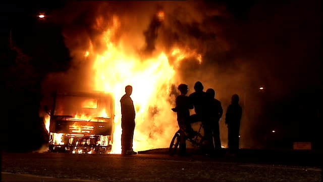 county armagh: lurgan: ext / night various shots of burning vehicle in road as youths stand by and watch - county armagh stock videos & royalty-free footage