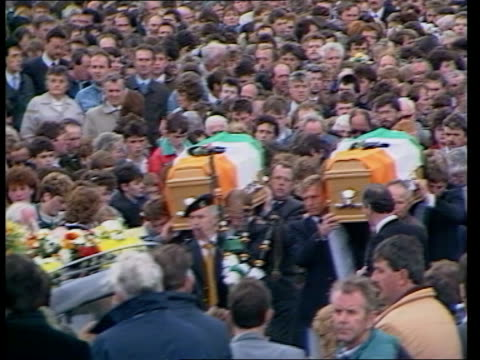 County Tyrone EXT MS RUC men in riot gear walk towards as mourners on bank and road in b/g MS RUC men in riot gear PULL OUT lining road MS Coffin...
