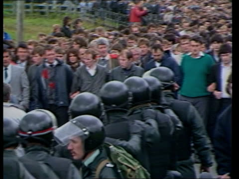 county tyrone loughmacrory ext ms ruc men in riot gear walk towards as mourners on bank and road in b/g tms coffins carried surrounded by crowd of... - northern ireland stock videos & royalty-free footage