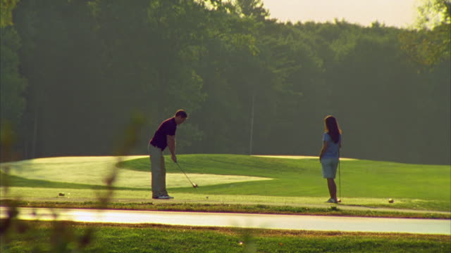 ws, coupe playing golf on golf course at sunset , seco, maine, usa - teeing off stock videos & royalty-free footage